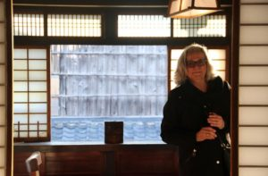 Jane King Hession stands in front of a window with Japanese screens