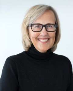 Portrait photograph of Julie Snow in black glasses and black sweater